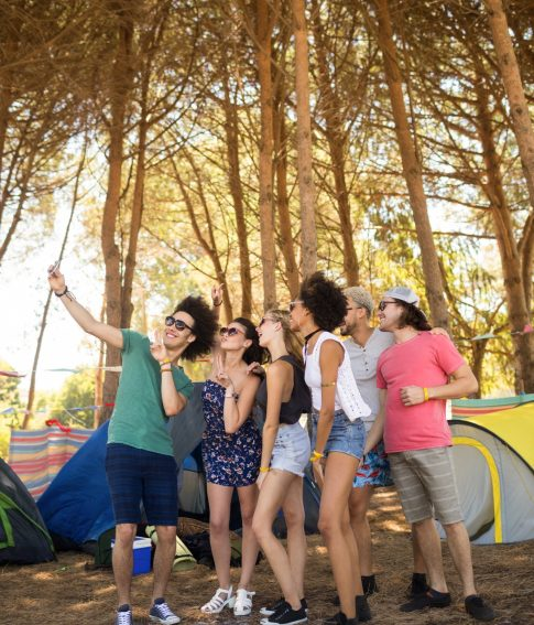 Full length of cheerful friends taking selfie at campsite